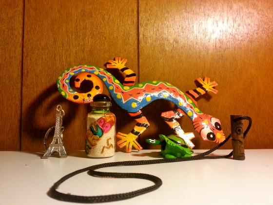 A multicolored lizard decal from Dominican republic , sand in a decorative bottle from Aruba, a bobble-head turtle also from Aruba, and a hand-carved necklace from Curacao. Also, an Eiffel Tower key chain that I've had for years